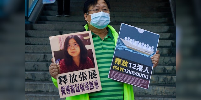 A pro-democracy activist holds placards with a photo of Chinese journalist Zhang Zhan outside the Chinese central government liaison office in Hong Kong.  (AP Photo / Kin Cheung)