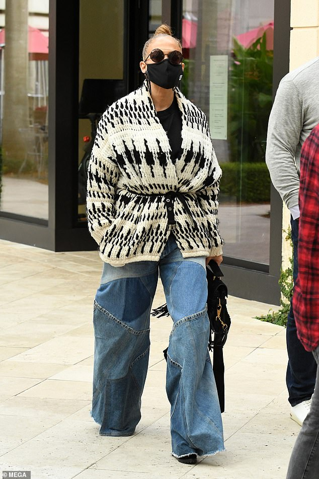 Superstar style: Lopez, 51, looked casual and chic in a pair of patchwork wide leg jeans and a chunky cardigan