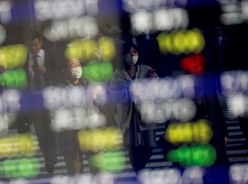 © Reuters.  File picture: Pedestrians wearing face masks are shown on an electrical panel showing stock prices outside a brokerage in a Tokyo commercial area